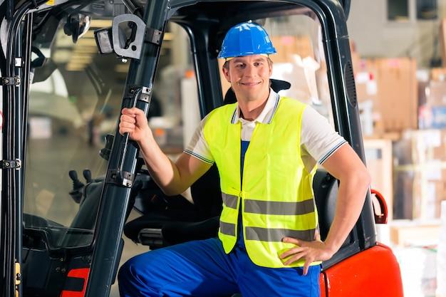 Autista di carrelli elevatori in giubbotto protettivo e carrello elevatore in piedi presso il magazzino della società di spedizioni,