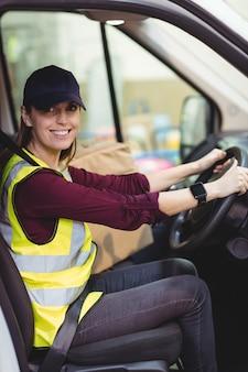 Autista di consegna guida furgone con pacchi sul sedile al di fuori del magazzino