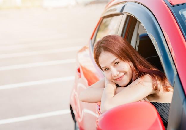 Autista donna asiatica in auto rossa