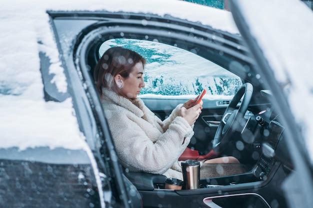 Autista donna attraente seduto dietro il volante della sua auto