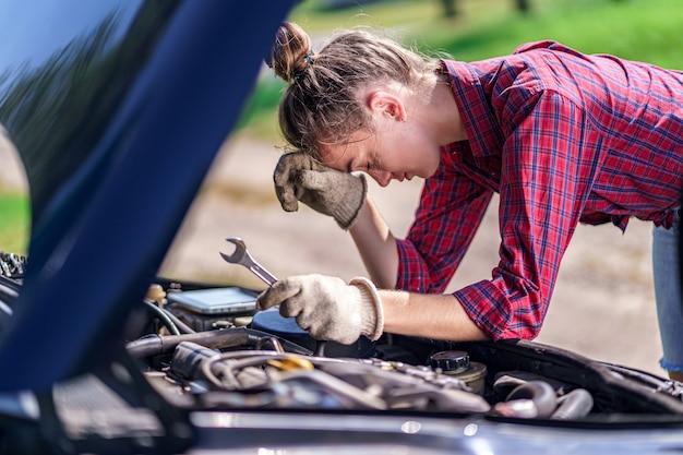 Autista donna stressato sconvolto infelice che ha problemi con l'automobile rotta durante un viaggio. necessità di assistenza e riparazione auto per motore guasto