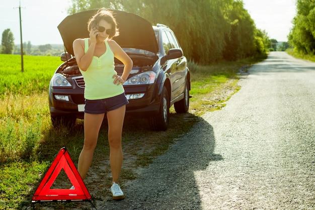 Autista frustrato della donna vicino ad un'automobile rotta