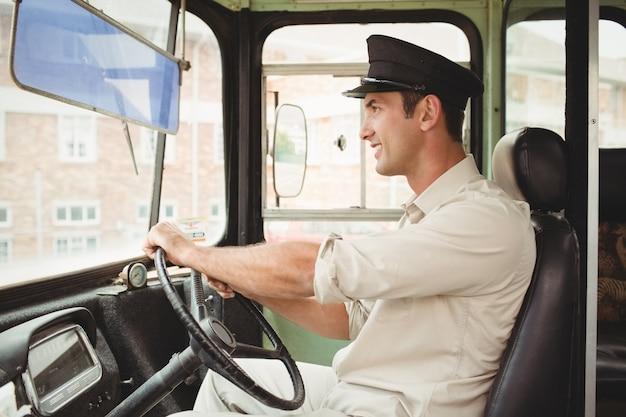 Autista sorridente che guida lo scuolabus