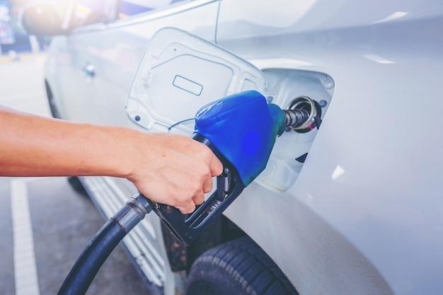 Auto bianca di rifornimento di auto con benzina alla stazione di servizio.