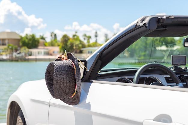 Auto convertibile con cappello appeso a uno specchio