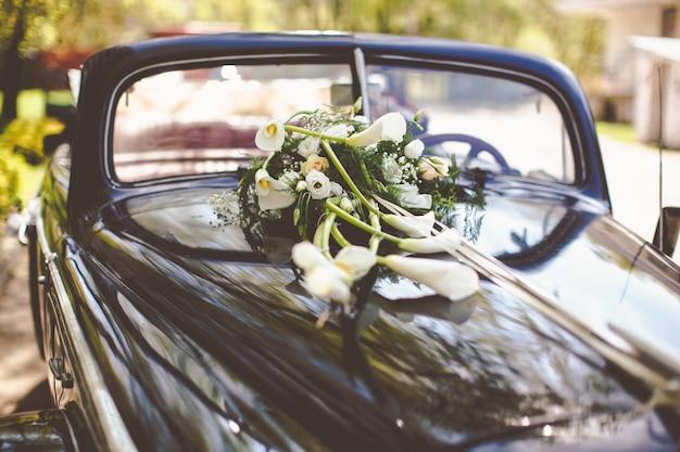 Auto d'epoca nera decorata con calle per un viaggio di nozze