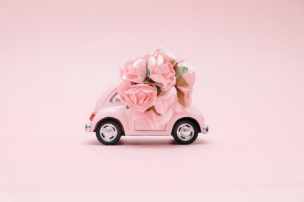 Auto giocattolo retrò rosa consegna mazzo di fiori