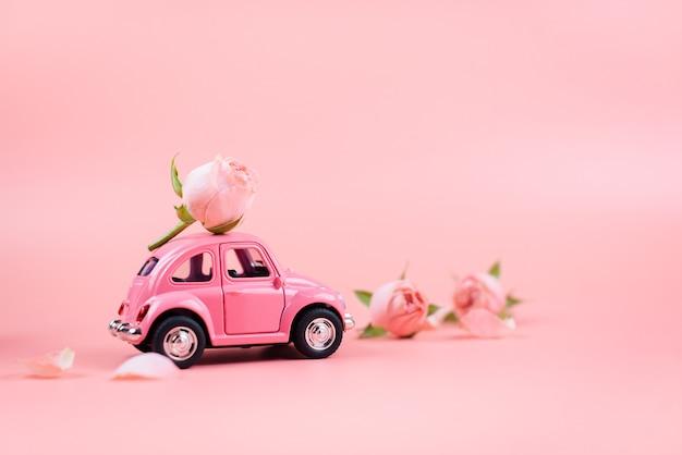 Auto giocattolo rosa retrò offre un fiore rosa su sfondo rosa.