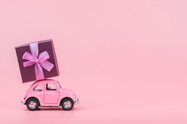 Auto giocattolo rosa retrò offre un regalo su sfondo rosa. cartolina del 14 febbraio, san valentino. consegna fiori giorno delle donne