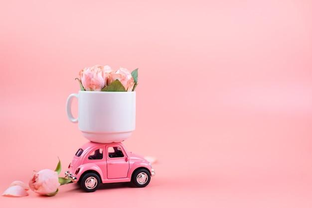 Auto giocattolo rosa retrò offre una tazza bianca con fiori su sfondo rosa. festa della mamma