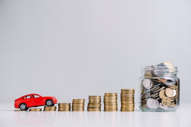 Auto guida su monete accatastate in aumento vicino barattolo di vetro