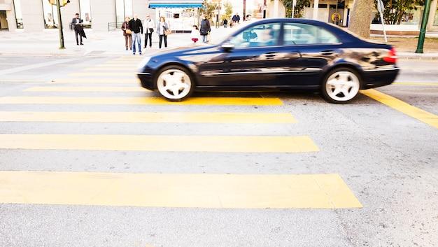 Auto nera guida su strada con strisce pedonali gialle