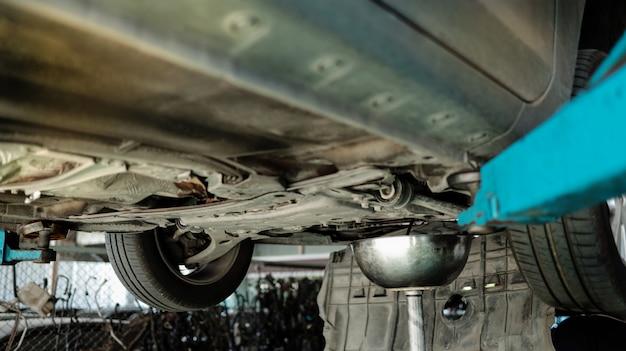 Auto sulla macchina di sollevamento presso la stazione di riparazione auto. servizi di riparazione e manutenzione. messa a fuoco selettiva