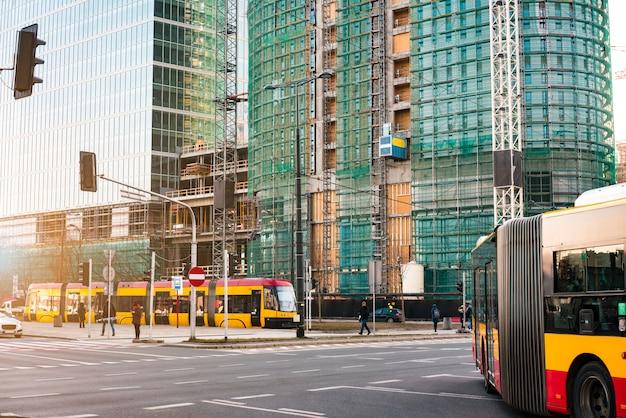 Autobus e tram pubblici passano davanti ai moderni grattacieli di vetro in costruzione.