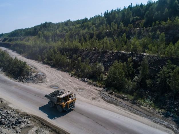 Autocarro con cassone ribaltabile industriale enorme in una cava di pietra caricata trasportando il marmo o il granito sparato da un fuco in natura