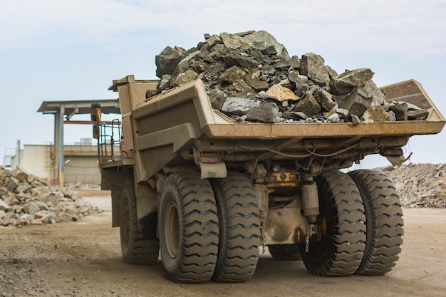 Autocarro con cassone ribaltabile industriale enorme vista posteriore a pieno carico nell'angolo basso della cava di pietra