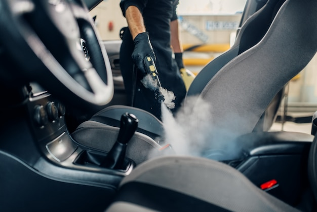 Autolavaggio, il lavoratore pulisce i sedili con un pulitore a vapore
