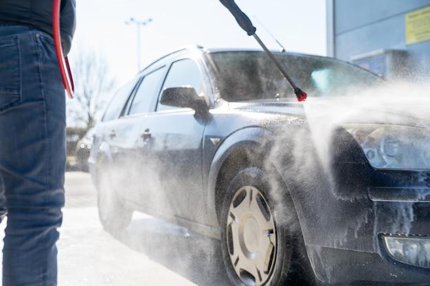 Autolavaggio manuale spruzzando acqua trattata ad alta pressione. autolavaggio veloce self-service