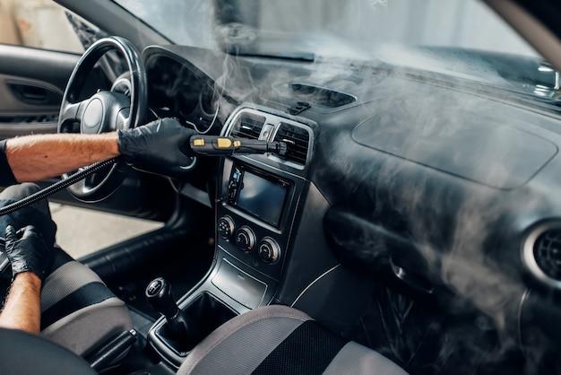 Autolavaggio, operaio pulisce salone con pulitore a vapore
