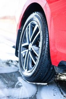 Autolavaggio, pulire l'auto dopo il lavaggio con schiuma. primo piano della ruota