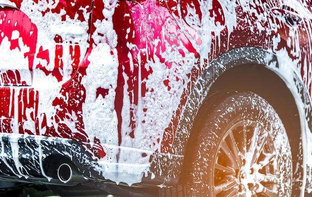 Autolavaggio suv compatto rosso con schiuma prima della ceratura del vetro e del rivestimento in vetro dell'automobile.