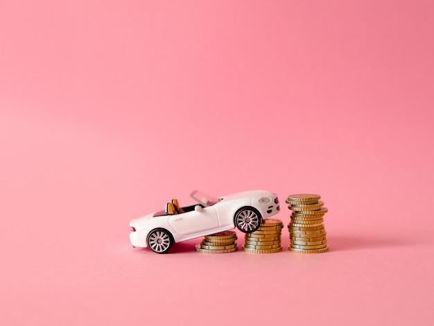 Automobile bianca del giocattolo situata sulle monete su fondo rosa. concetto di credito o vendita per l'automobile.
