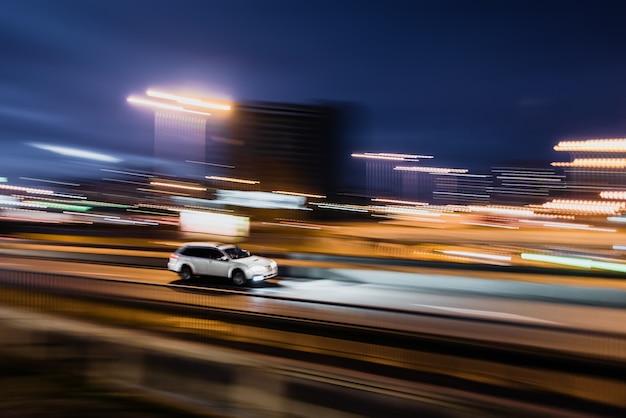 Automobile bianca sfocata sul movimento di velocità