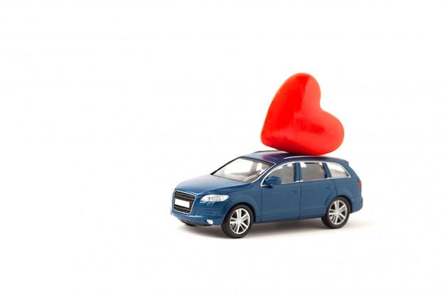 Automobile blu del giocattolo di suv che consegna cuore su fondo bianco