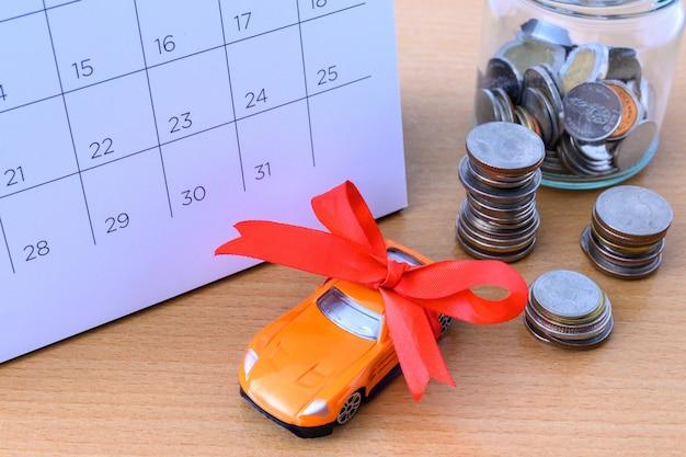 Automobile con il nastro sul calendario, nuovo concetto dell'automobile