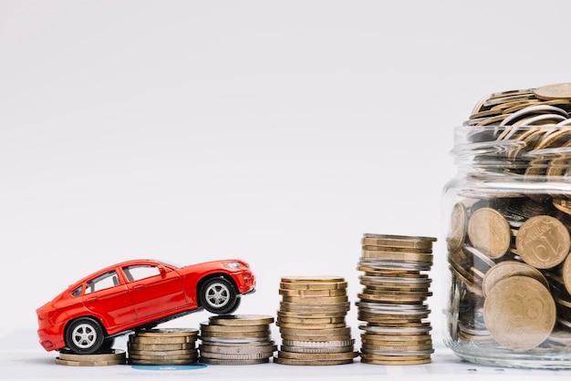 Automobile del giocattolo che va sulla pila crescente di monete vicino al barattolo delle monete contro fondo bianco