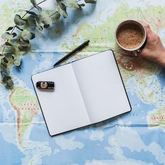 Automobile del giocattolo sulla tazza di caffè della tenuta della mano e del diario in bianco sopra la mappa di mondo