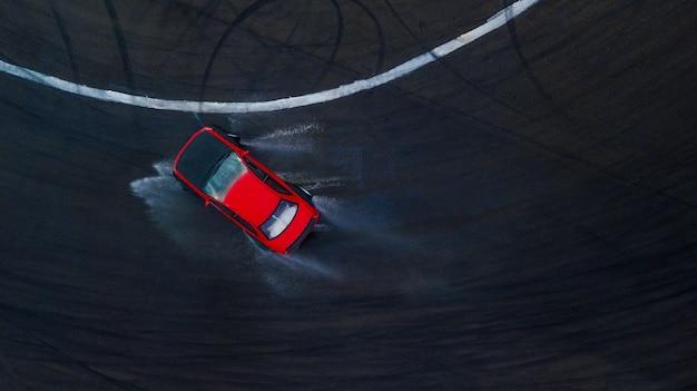 Automobile di spostamento dell'autista professionale di vista superiore aerea sulla pista di corsa bagnata, con la spruzzata dell'acqua, automobile rossa.