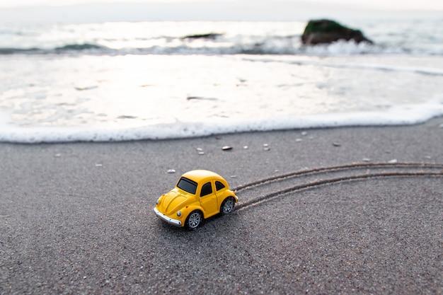 Automobile gialla del giocattolo sulla spiaggia alla luce solare di estate.