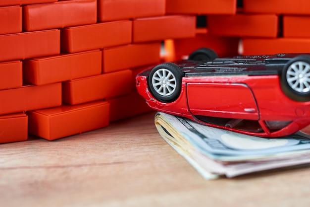 Automobile invertita sul mucchio delle banconote in dollari. concetto di assicurazione auto, danni dopo l'incidente
