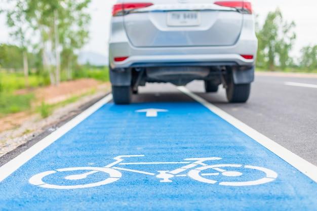 Automobile moderna sul segno bianco della bicicletta