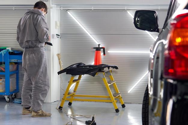 Automobile nell'officina riparazioni automatica con il meccanico su un fondo
