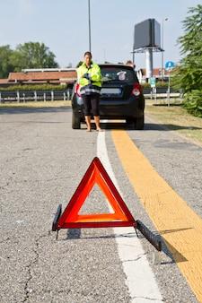 Automobile ripartita con il triangolo d'avvertimento rosso