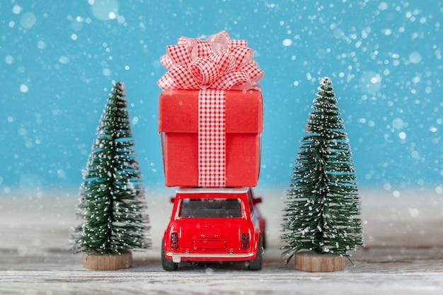 Automobile rossa che porta sul tetto un contenitore di regalo e un albero di natale. concetto di natale e capodanno