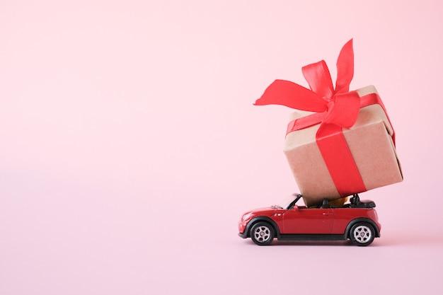 Automobile rossa del giocattolo che trasporta il contenitore di regalo con il nastro rosso