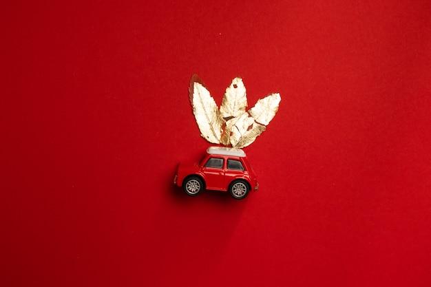 Automobile rossa del giocattolo della composizione c di saluto festivo e oro delle foglie su un fondo rosso.