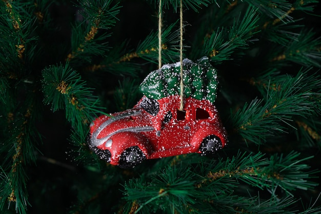 Automobile rossa del giocattolo di natale sull'albero di nuovo anno. composizione di natale.