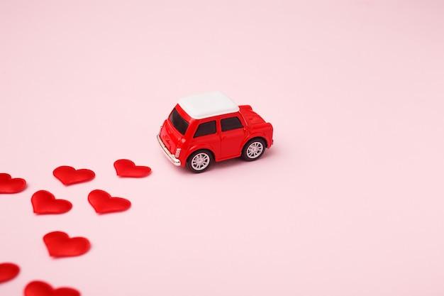 Automobile rossa del retro giocattolo rosso con l'arco rosso per il san valentino sul rosa con i coriandoli del cuore