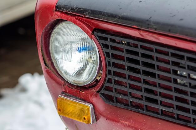 Automobile rossa dell'annata su un festival di vecchie automobili. fine del faro della retro automobile in su.