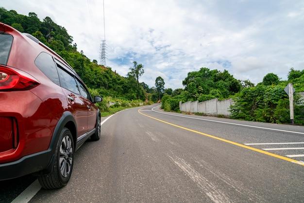 Automobile rossa di suv sulla strada asfaltata con il trasporto della foresta di verde della montagna per viaggiare concetto