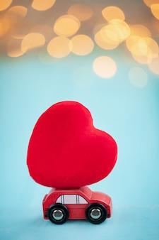 Automobile rossa in miniatura che trasporta un cuore rosso