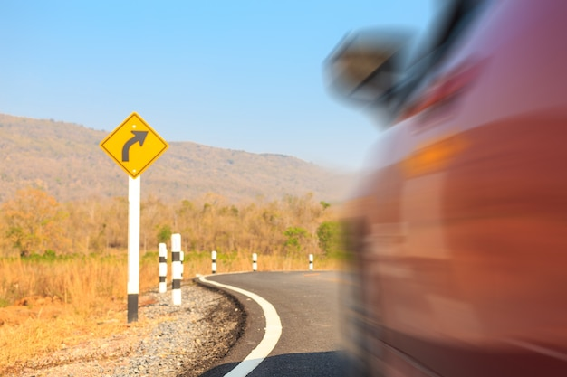 Automobile rossa sulla strada con il segno giusto della sterna. concetto per il trasporto