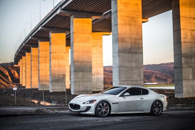 Automobile sportiva bianca del coupé che parcheggia sotto il ponte.