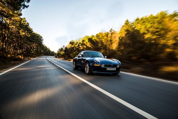 Automobile sportiva di lusso nera che guida attraverso la foresta.