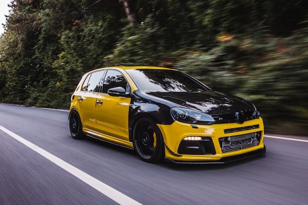 Automobile sportiva gialla con autotuning nero. vista laterale.