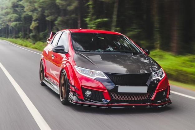 Automobile sportiva rossa con autotuning nero sulla strada.